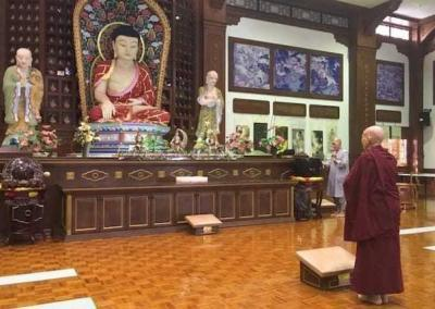 Nun standing before statue in temple