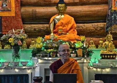 nun sitting i fron to Buddha Statue