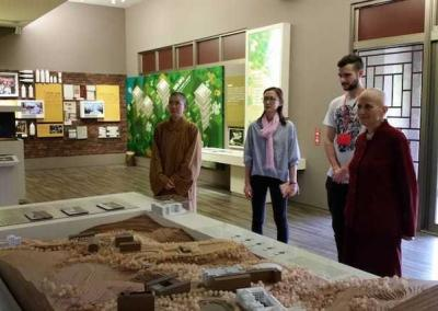 Four people looking at scale model of buildings