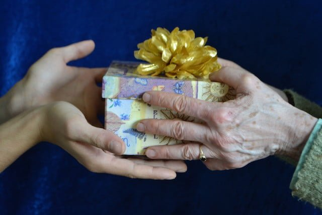 young hands take gift wrapped box from older hands