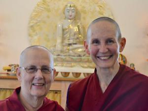Two smiling buddhist nuns in front of white Buddha.