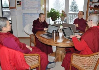nuns sitting around a table with laptops