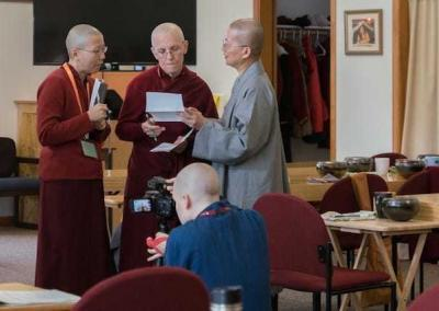 Vens. Damcho and Semkye confer with instructor Ven. Jenkir on the schedule.