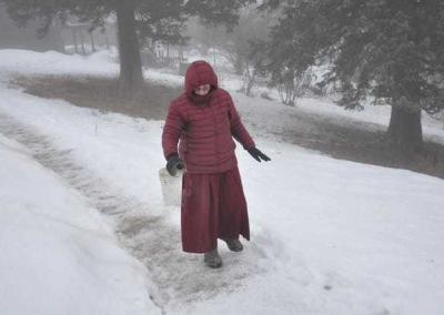 Ven. Sherab Drolma from Argentina spreads gravel on the icy paths.