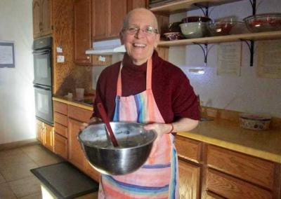 smiling nun with bowl in kitchen