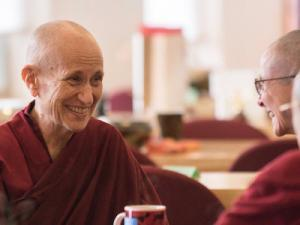 Smiling Buddhist nuns greet each other.