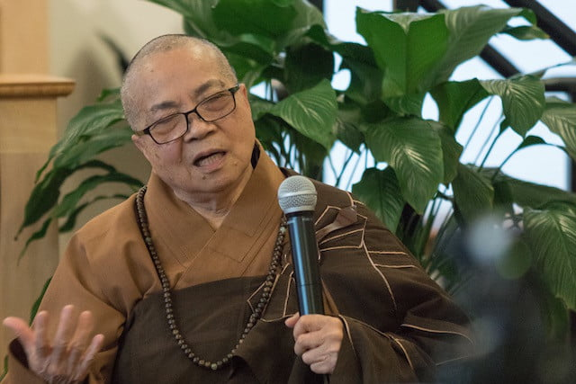 Older Chinese nun with microphone in hand