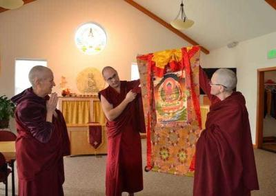 Vens. Chonyi and Donyo, who offered service during the Vinaya course, offer an Amitabha thangka (painting).