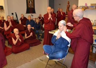 The sangha chants as the ritual head shaving begins.