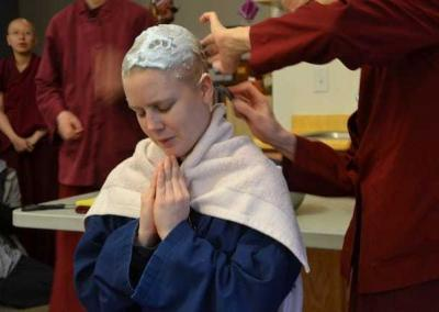 As preceptor, Ven. Thubten Chodron takes the first and last turns with the razor. Shaving the hair symbolizes Rebecca's determination to cut off the bonds of attachment.