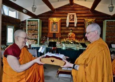 Ven. Tsultrim, the karma master, gives the robe to Ven. Jigme who is the robe keeper this year.