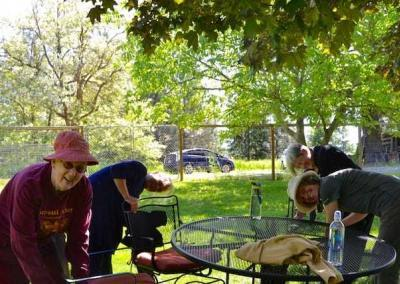 Ven. Jigme leads Bernie and our German guests, Sonya and Edith, to wax the outdoor furniture.