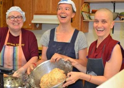 """Patty Jo, Fabienne, and Ven. Jampa enjoy """"beating up the bread,"""" an activity that incorporated into a skit at the end of EML"""