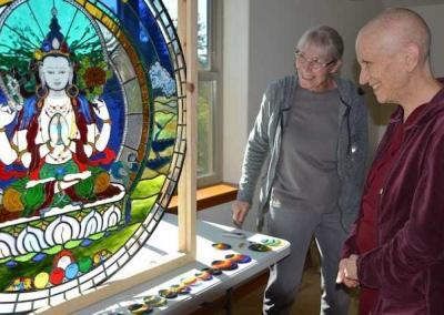 Bev and Ven. Chodron look upon the beautiful stained-glass window.