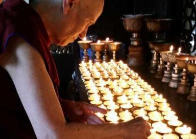 Ven. Chodron makes light offerings at the main temple in Dharamsala.