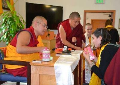 Along with all the guests, Dinae receives a blessed cord and altar card from Rinpoche.