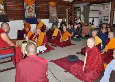 A small crowd welcomes Rinpoche to the only log cabin Meditation Hall in the world.