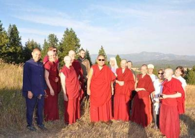 Rinpoche enjoys the far view from the upper meadow before taking a drive into the forest along the Bodhisattva Loop.