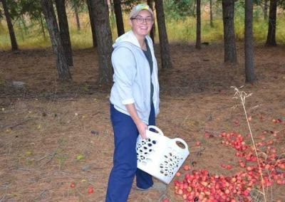 Em collects crabapples for the deer in the forest.