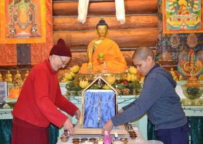 Ven. Tsepal and Anagarika Christina place the mandala house for 1000-Armed Chenrezig into the Meditation Hall.