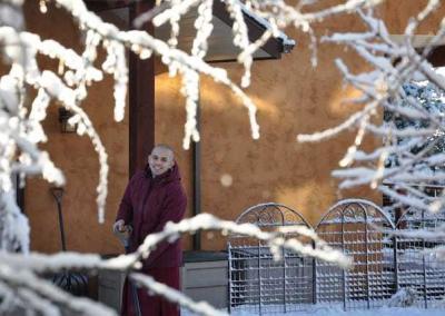 Ven. Tenzin joyously helps with shoveling snow.