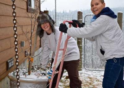 Em and Christina store huge flowerpots safely beside Shanti Cabin.