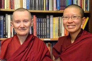 Two Buddhist nuns with bookshelves behind them.