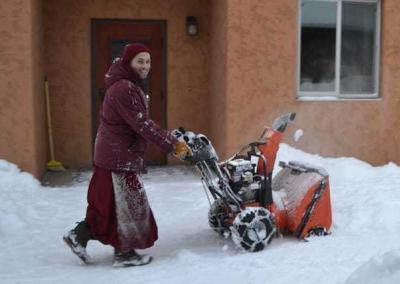 Ven. Tenzin runs the snow blower with great enthusiasm.