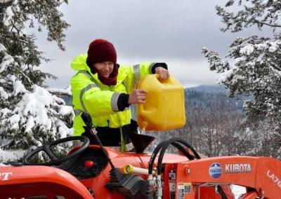 Ven. Losang fills the tractor with gasoline so he can remove snow from the Abbey roads.