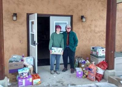 Every week kind volunteers came up the hill to offer food, even under harsh weather conditions. Em and Maeve help unload at the front door.