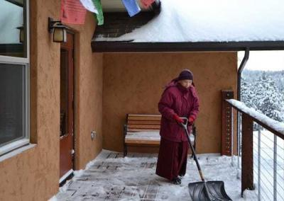 With great mindfulness, Ven. Pende shovels snow from Chenrezig Hall deck.