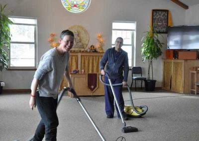 Fabienne and Christina, with enormous joyous effort, vacuum the dining room.