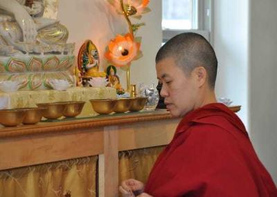 Ven. Pema prepares the altar for a puja.