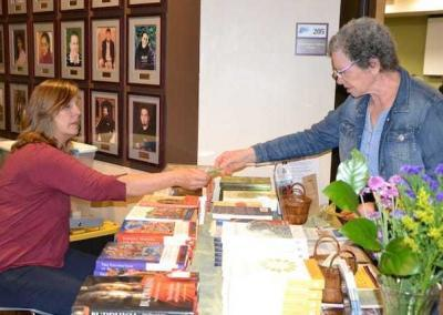 CdA Dharma Friends set up a book table at the NIC talk, where Janet accepts an offering for the Abbey