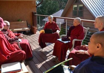 monastics sitting on a deck
