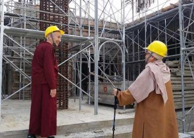 nuns in hard hats in building site