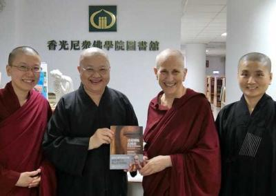 """Luminary's librarians show Venerable the  Chinese translation of """"Buddhism: One Teacher, Many Traditions."""""""