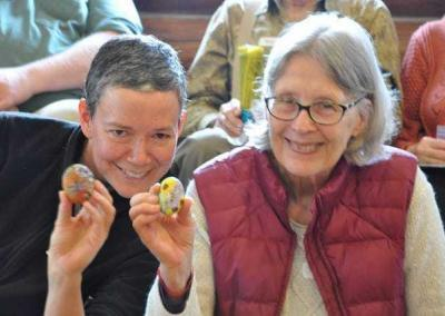Fabienne and Sherran receive beautiful painted stones that Cheri Langston offered to the Abbey.