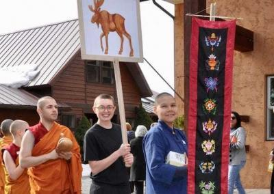 laypeople and monastics with moose placard