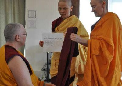 Nun offering robe to seated nun