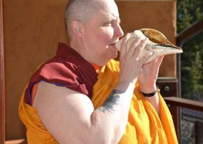 Ven. Tsultrim blows the conch signaling bhikshunis—the fully ordained nuns—to assemble.