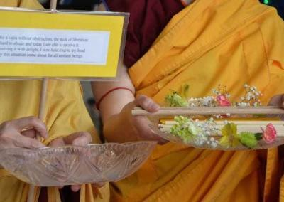 """Monastics recite a verse to receive the stick: """"Like a vajra without obstruction, the stick of liberation is hard to obtain and today I am able to receive it. Receiving it with delight, I now hold it up to my head. May this situation come about for all sentient beings."""""""