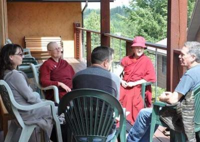 Sharing the Dharma Day discussion on a beautiful spring day on the veranda of Chenrezig Hall.
