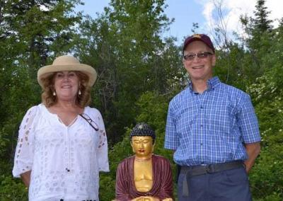 lay man and woman with Buddha statue