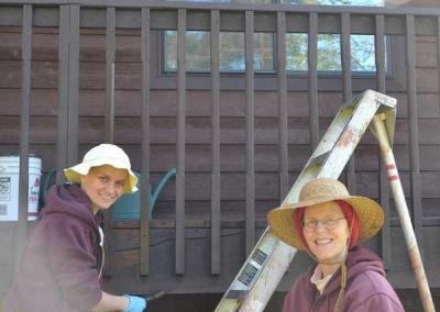 two smiling nuns painting a deck.