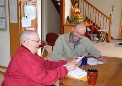nun and lay man at a table
