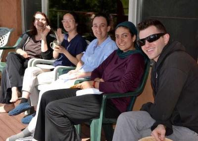 Young adults enjoy tea on the deck.