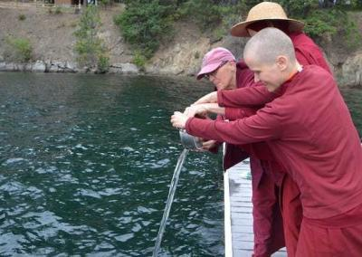 nuns pouring water into a lake