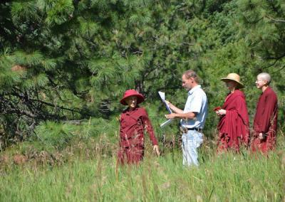 Ven. Chodron shows Tim and the team—Ven. Tarpa, Ven. Damcho, and Ven. Samten— the area for for the new building.