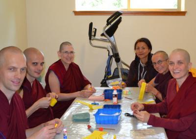 Ven. Jampa teaches how to roll mantras. These will be used later to fill Buddha statues.